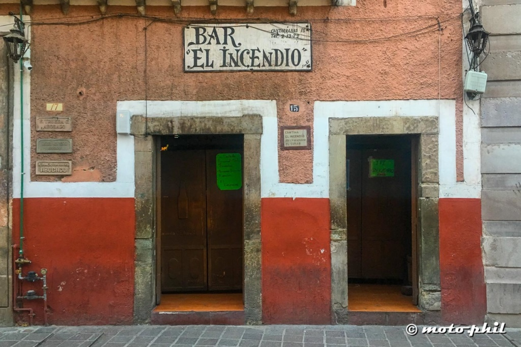 Entrace doors to Bar El Incendio on a red and orange wall with white accents