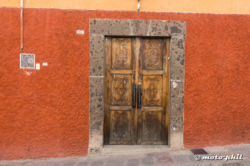 Beautiful colonial wooden door in a red wall in San Miguel de Allende