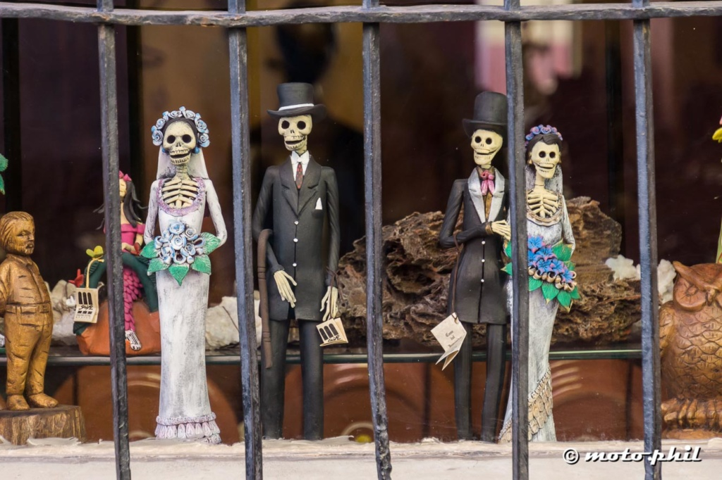 Dia de los muertos couple figures behind iron bars